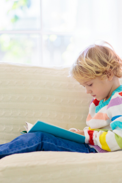 Boy Reading Book On A Couch