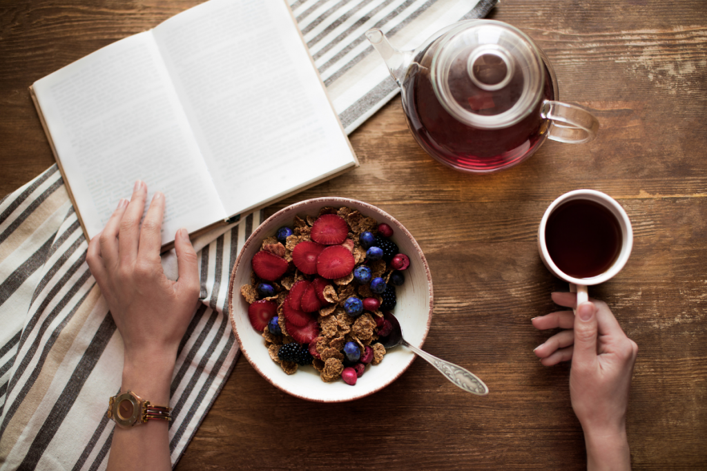 Best Books for Homeschooling Inspiration - Stock photo hands, book, cereal, tea on a wooden table