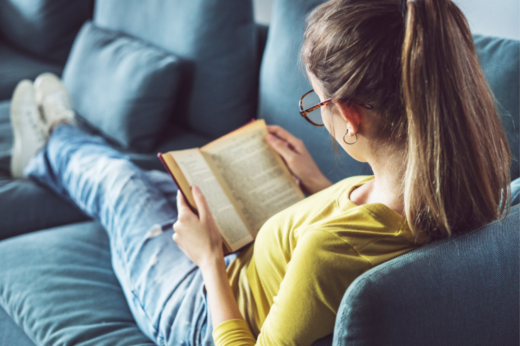 Best Books For Homeschool Inspiration Stock Photo - Woman in glasses reading a book on a blue couch