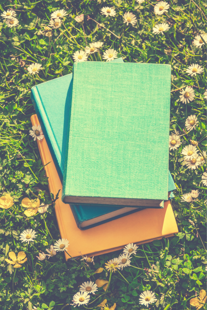 9 Books Every Teen Girl Should Read - Stock Photo, stack of 3 books laying on grass and white flowers