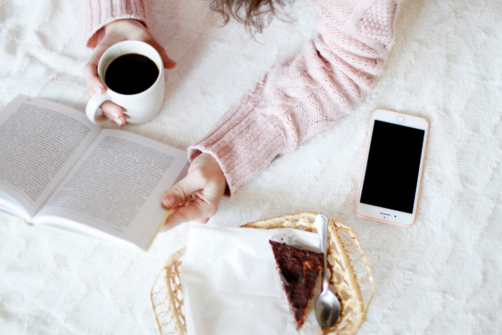 Encouraging Books For Christian Mothers - Stock Photo, Woman Reading Book with coffee, phone, and snack