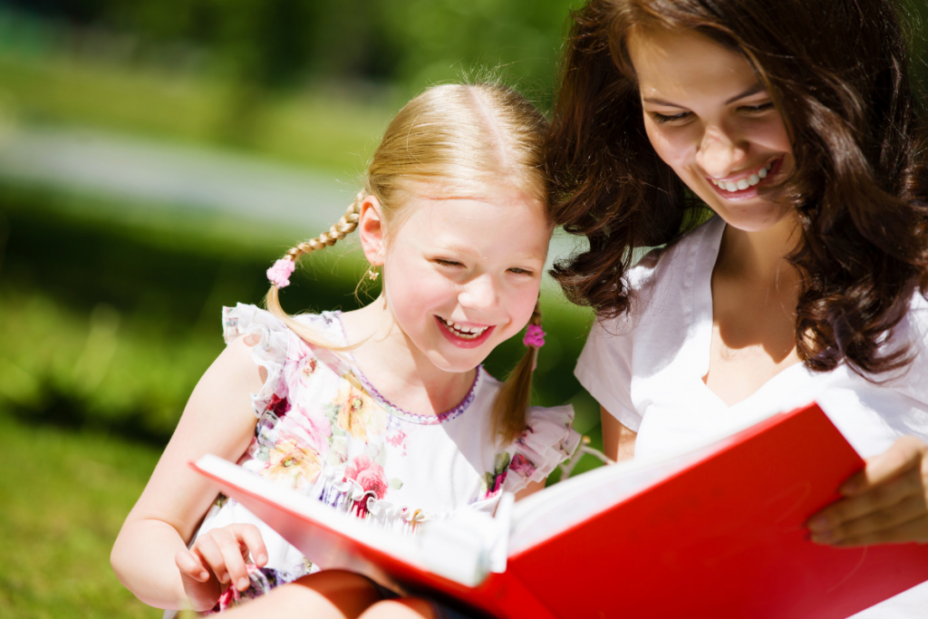 Mom reading with her daughter outside