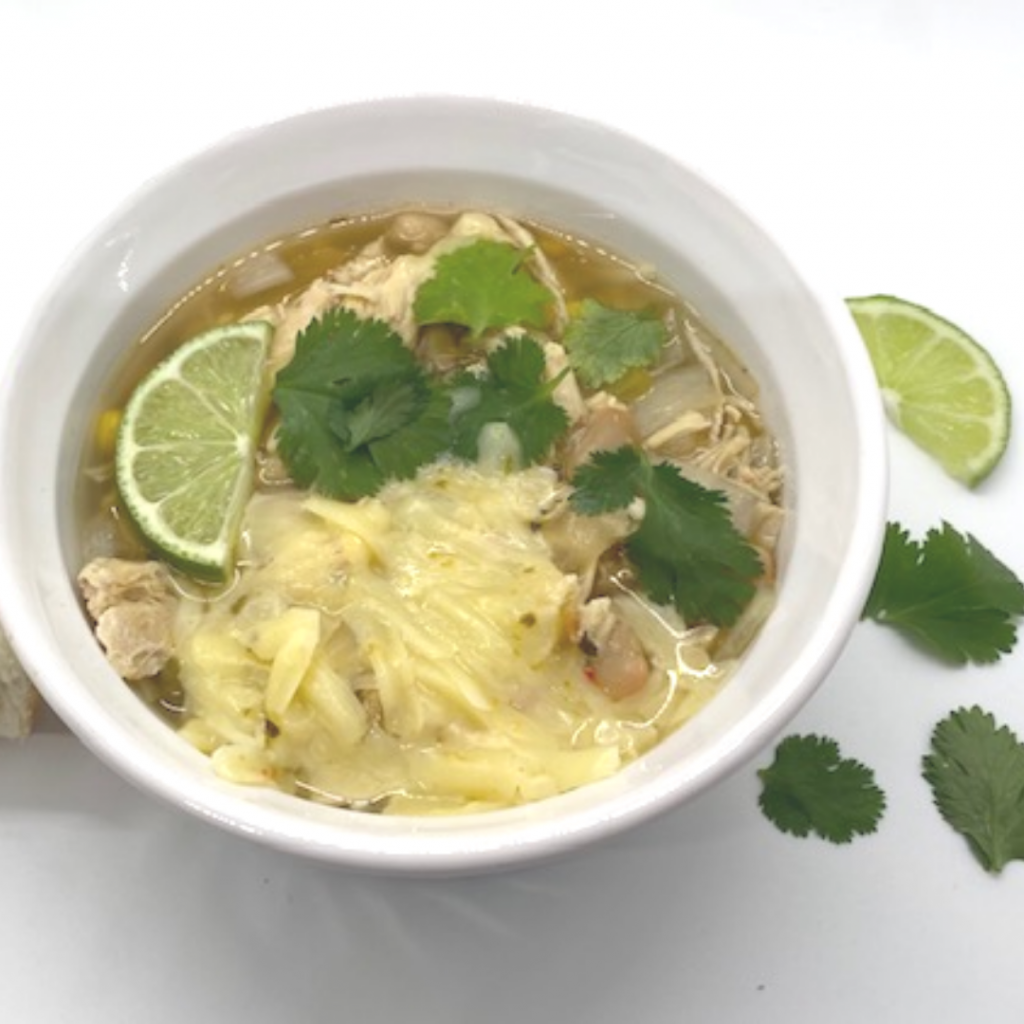 Bowl of white chicken chili covered with cheese.